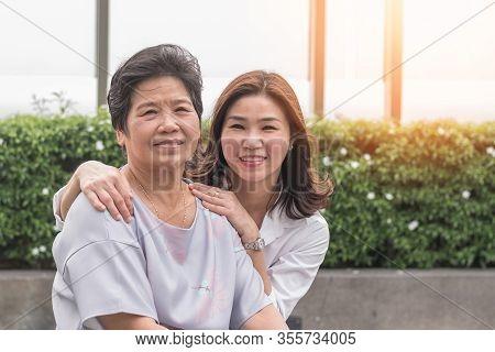 Elderly Senior Woman (aging Old Adult Person) With Caregiver Or Caretaker Nurse In Nursing Hospice H