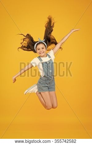 Energy Inside. Small Girl Jump Yellow Background. Enjoy Freedom. Childrens Day Concept. Spirit Of Fr