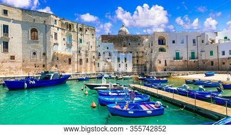 Traditional Italy - white town Monopoli with colorful fishinng boats. Puglia region