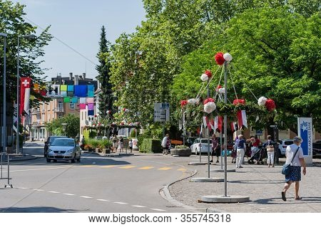 People Walking Through The Main Street Of Brugg Decorated With Red And White Paper Flower At Jugendf