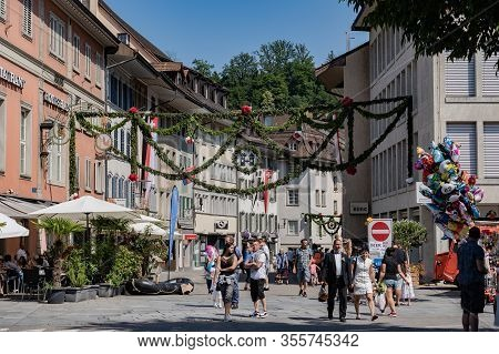 People Walking Through The Old Town Of Brugg After Rutenzug, Decorated With Pine And Paper Flower An