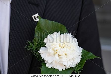 Flower Decoration For Man On Dark Blue Blazer With A White Pin With A Coat Of Arms With The Tower Of