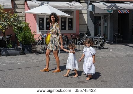 Young Mother With Two White Dressed Little Girls Walking At Sunny Day Through The Streets Of The Old