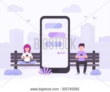 Young Woman And Young Man Sitting In City Park Near Big Smartphone With The Message Bubbles On Scree