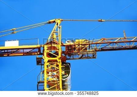 Crane. Self-erection Crane Against Blue Sky. Industrial Background.