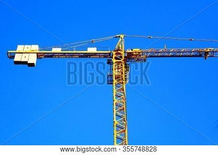 Crane. Self-erection Crane Near Against Blue Sky. Construction Site.