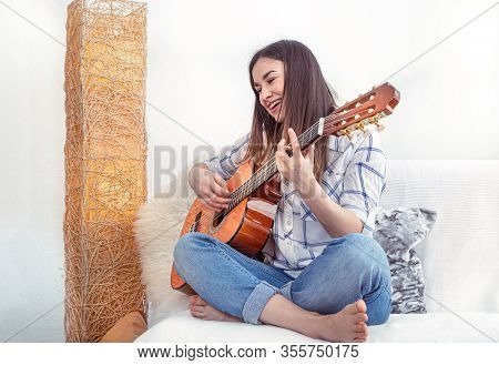 A Young Woman In The Living Room With A Guitar Sits On A Light Sofa And Plays .
