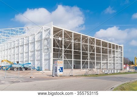 Oldenzaal, Netherlands - March 14, 2020: Frame Of A Newly Built Warehouse Against A Nice Blue Sky