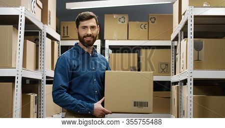 Portrait Of Handsome Young Male Courier In Smiling Cheerfully To Camera In Postal Storage Of Parcels