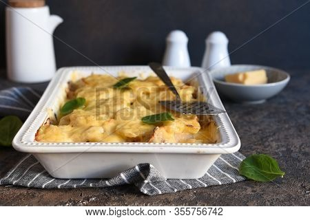 Casserole With Potatoes, Mushrooms And Cheese On The Kitchen Table. Horizontal Focus.