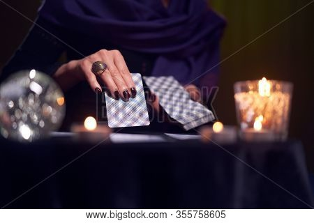 Close-up of woman fortuneteller's hands with cards at table with candles, magic ball in dark room