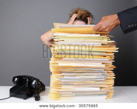 A frazzled female office worker grabs her head in frustration as her boss piles more work on her desk. Horizontal format over a gray background.