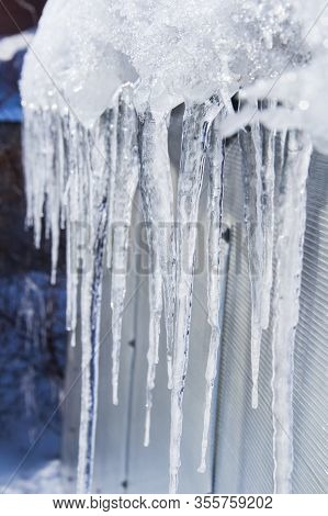The Icicles Are Melting. Spring Thaw. Warm Winter . Icicles Close Up. Close Up Of A Large Wavy Icicl