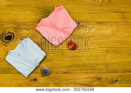 Baby Clothes And Pacifier For Boy And Girl On Wooden Table.baby Announcement Concept.
