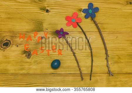 Happy Easter Message With Painted Eggs And Flowers On Wooden Table.