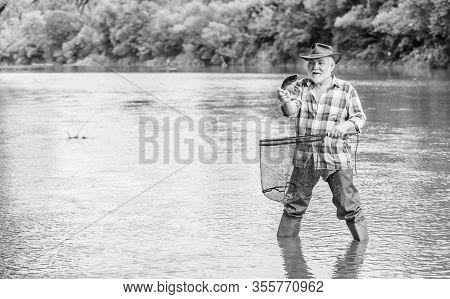 Fisherman Fishing Equipment. Fisherman Alone Stand In River Water. Pensioner Leisure. Man Senior Bea