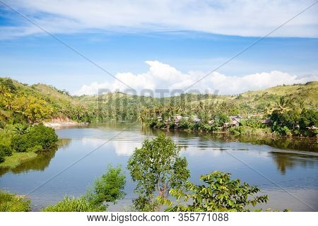 Countryside On A Large Tropical Island. Small Village On The Green Hills By The River. Tropical Land