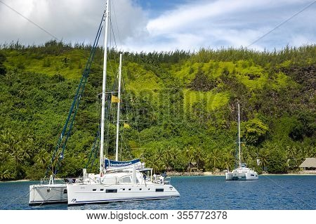 French Polynesia, Papeete, December, 27, 2017 - Several Catamarans In A Calm Blue Lagoon Near The Is