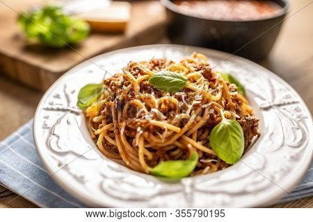 Italian Pasta Spaghetti Bolognese Served On White Plate With Parmesan Cheese And Basil.
