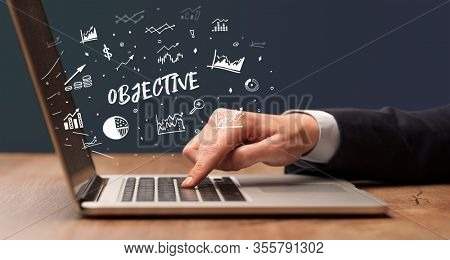 Businessman working on laptop with OBJECTIVE inscription, modern business concept