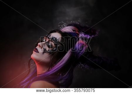 Portrait Of A Devil Girl Wearing Scary Fantasy Make Up And Violet Horns Posing In A Dark Studio On A