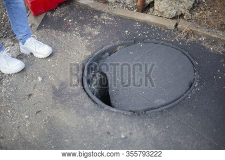 Open Sewer Manhole. Dangerous Failure In The Earth. Hole In The Pavement. The Girl Steps Into A Dang