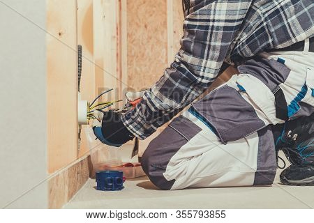 Electrician And His Work During House Development. Electric Outlet Point Installation.