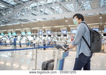 Asian Man Wear Face Mask Walking With Airport Trolley And Suitcase Luggage In Airport Terminal. Coro
