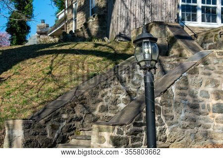 A Lightpost With A Stone Pathway Behind It