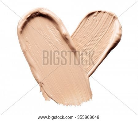 Foundation smear close-up. Foundation face make-up smudge, smears. Cosmetic liquid bb cream beige color heart shaped stroke. Make up texture, concealer isolated on white background. Love cosmetics
