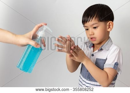 Asian Mom Using Alcohol Antiseptic Gel For Cleaning Baby Hands To Prevent Against Infection Of Covid