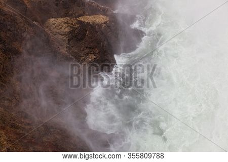 Looking Down To The Base Of Lower Falls In The Yellowstone River As Waves And Mist Interact With The