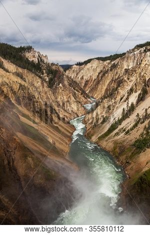 Looking Down The Yellowstone River From The Top Of Lower Falls As Mist Rises And The Rapids Cut A Pa