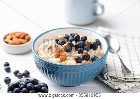 Bowl Of Oatmeal Porridge With Blueberries And Almond Nuts On White Table. Healthy Breakfast Food, Cl