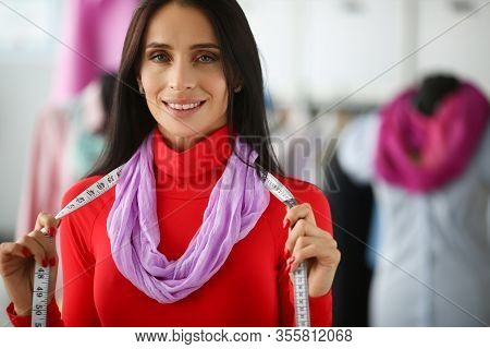 Woman With Measuring Tape On Neck, Tailors Device. Fashion Designer At Workplace, Smiles And Holds T