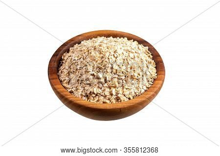 Raw Oat-flakes In Wooden Bowl. Isolated On White Background. Uncooked Dry Rolled Oatmeal.