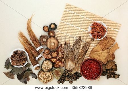 Chinese herb and spice collection  used in traditional herbal medicine on bamboo mat and mottled cream background.