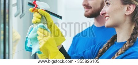 Team of commercial cleaners working in an office cleaning the windows