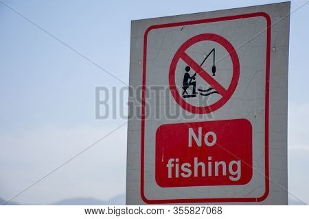 No Fishing Sign In Red And White Aluminum On Blue Sky Background To Ban Recreational Activity For Co