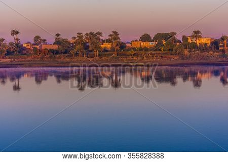 Sunrise Over The West Bank Of The Nile In Egypt. Between Luxor And Aswan. The Sky Glows In Pink And