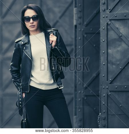 Young fashion woman in sunglasses on city street Stylish female model in black leather jacket and skinny jeans