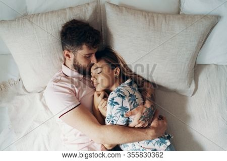Couple In Love Is Embracing On The Bed. Man Hugging And Kissing His Girlfriend. Top View