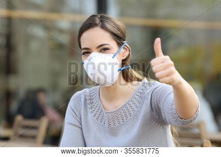 Woman Doing Thumbs Up Gesture Wearing A Protective Mask Avoiding Contagion On A Terrace