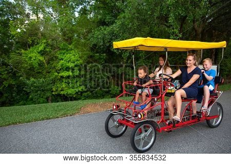 Young happy family riding a double surrey tandem bicycle together. Outdoor summer fun with kids