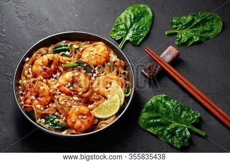 Prawn Pad See Ew In Black Bowl At Dark Slate Background. Pad See Ew Is Thai Cuisine Dish With Rice N