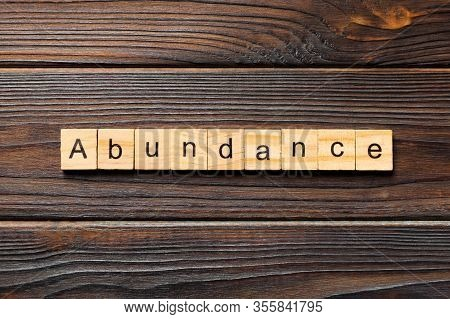Abundance Word Written On Wood Block. Abundance Text On Wooden Table For Your Desing, Top View Conce