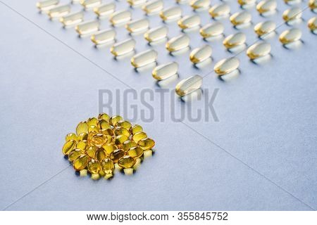 Yellow Capsules With Vitamin D On A Blue Background. Sunshine Vitamin.