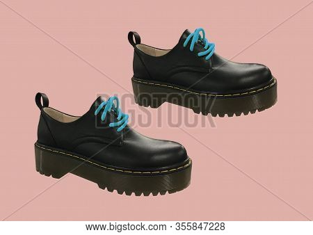 Black Leather Platform Shoes Isolated On Pink Background. Classic Shoes On A High Black Tractor Plat