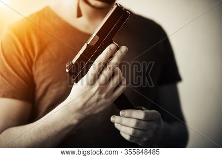 An Unkind Man In A T-shirt Stands In The Gloom With A Gun In His Hands And Changes The Magazine In I