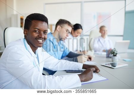 Portrait Of Young African-american Doctor Smiling At Camera During Medical Council Or Conference In